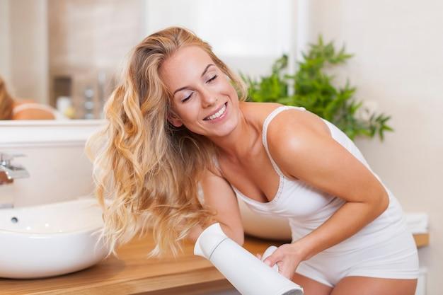 Radość piękna blond kobieta podczas suszenia włosów