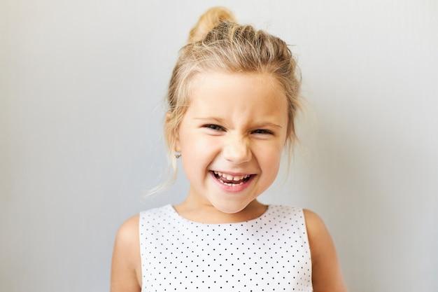 Radość, pozytywne emocje i koncepcja szczęśliwego dzieciństwa. piękna urocza dziewczynka wykrzykuje z podekscytowaniem, jest uszczęśliwiona, ponieważ idzie do parku rozrywki, kina lub na zakupy, śmiejąc się głośno
