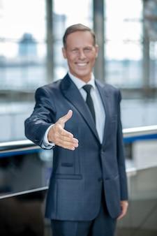 Radość spotkania. radosny, sympatyczny mężczyzna w ciemnym formalnym garniturze i krawacie wyciąga rękę do uścisku dłoni podczas spotkania na lotnisku