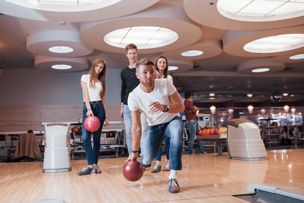Radość z gry. młodzi weseli przyjaciele bawią się w weekendy w kręgielni