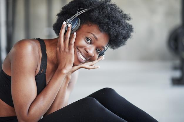 Radość z muzyki. afroamerykanka z kręconymi włosami i sportowym ubraniem ma dzień fitness na siłowni