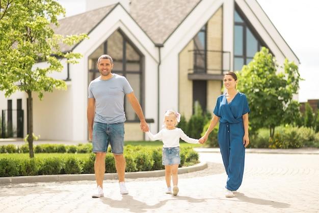 Radość ze wspólnego spaceru. śliczna urocza córka trzymająca rodziców za ręce podczas wspólnego spaceru walk