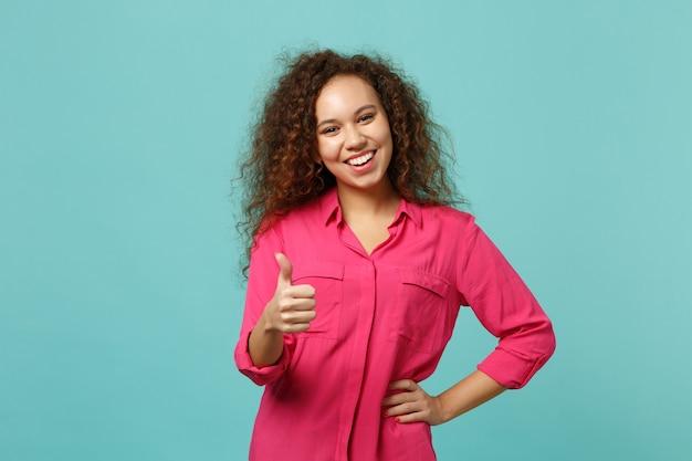 Radosna african american dziewczyna w ubranie wyświetlono kciuk w górę, patrząc aparat na białym tle na tle niebieskiej ściany turkus w studio. ludzie szczere emocje, koncepcja stylu życia. makieta miejsca na kopię.