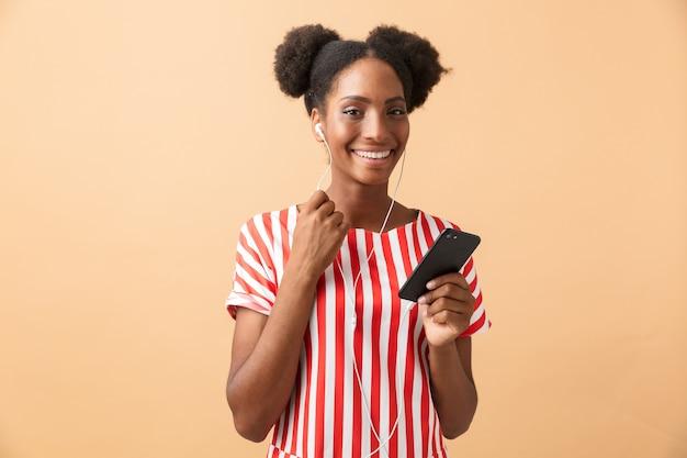 Radosna afroamerykanin kobieta w ubranie, słuchanie muzyki na smartfonie z białymi słuchawkami, na białym tle
