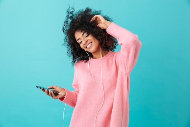 Radosna amerykanka w swobodnym stroju tańczy i słucha muzyki z przyjemnością przez białe słuchawki, odizolowane na niebieskiej ścianie