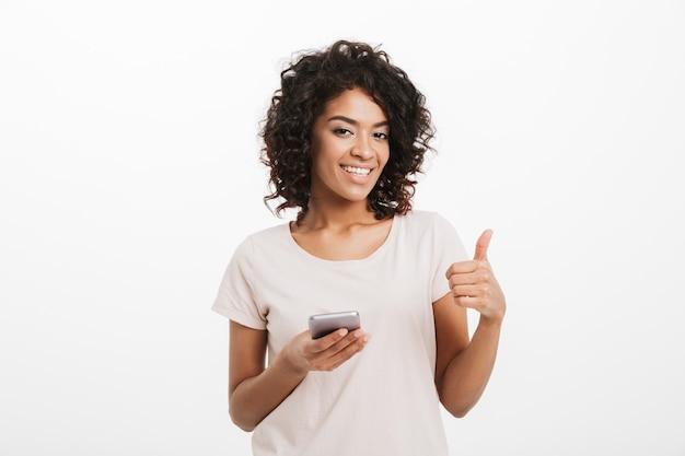 Radosna amerykańska kobieta z fryzurą afro i dużym uśmiechem na czacie przy użyciu telefonu komórkowego i pokazując kciuk do góry, odizolowane na białej ścianie