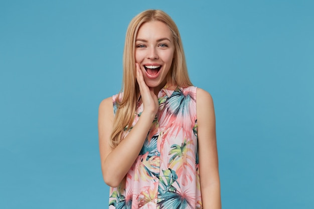 Radosna atrakcyjna blondynka z długimi włosami w naturalnym makijażu, trzymająca dłoń na policzku i uśmiechająca się szeroko podczas pozowania