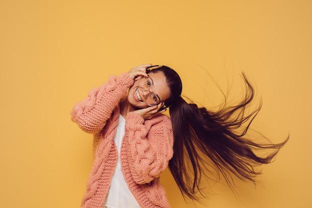 Radosna atrakcyjna brunetka w okularach i słuchawkach ubrana w różową bluzę z białym swetrem kręci głową z długimi fruwającymi włosami na żółtym tle. koncepcja pozytywnych ludzi.
