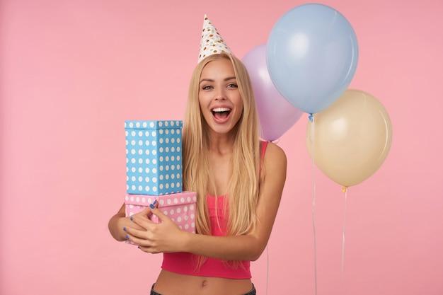 Radosna atrakcyjna młoda długowłosa kobieta w różowej bluzce i świątecznej czapce jest podekscytowana i zaskoczona prezentami urodzinowymi, pozując na różowym tle w wielokolorowych balonach