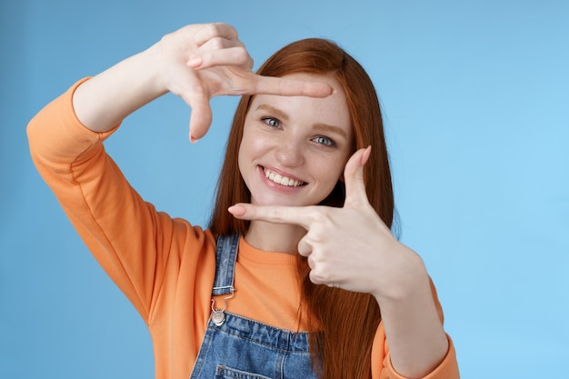 Radosna atrakcyjna szczera ruda młoda dziewczyna poszukująca inspiracji znajdź idealny kąt zrób dobre ujęcie spraw, by ramki dłoni wyglądały przez zachwycony rozbawiony uśmiechnięty szeroko białe zęby niebieskie tło