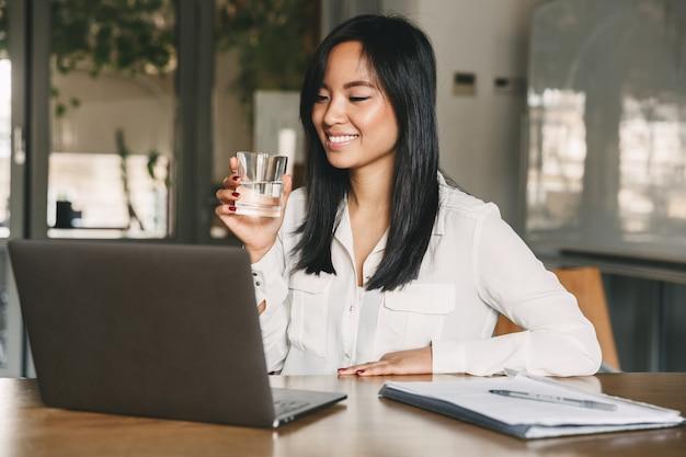 Radosna azjatycka kobieta w biurze lat 20. ubrana w białą koszulę, uśmiechnięta, patrząc na ekran laptopa i wodę pitną ze szkła