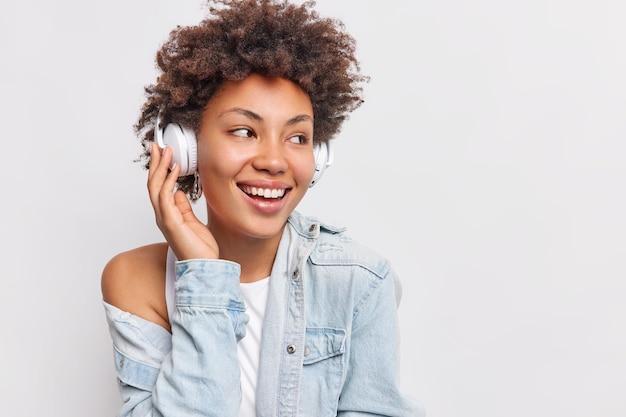 Radosna beztroska kobieta z kręconymi włosami odwraca wzrok uśmiech zęby nosi bezprzewodowe słuchawki stereo na uszach słucha ulubionej muzyki z playlisty cieszy się dobrą jakością dźwięku pozuje na białej ścianie wolne miejsce