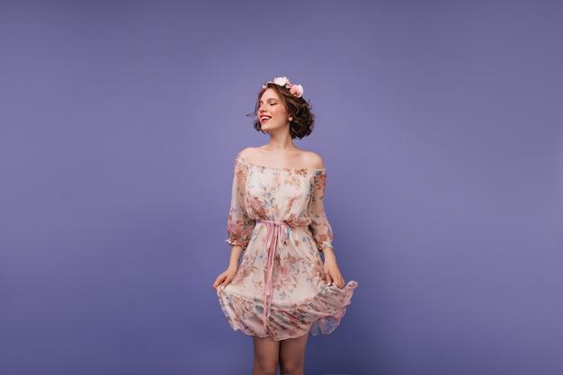 Radosna biała dziewczyna bawi się swoją romantyczną sukienką. wspaniała kędzierzawa dama z kwiatami na głowie.