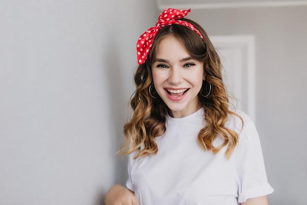 Radosna biała dziewczyna pozuje z podekscytowanym wyrazem twarzy. wewnątrz zdjęcie blithesome modelki z czerwoną wstążką w kręconych włosach.