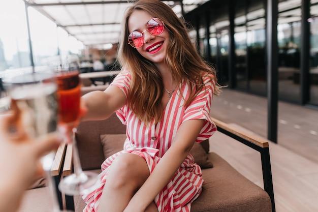 Radosna biała dziewczyna w letniej sukience spędza czas w kawiarni. portret zmysłowej kobiety blondynka w różowe okulary wyrażające szczęście w ciepły dzień.