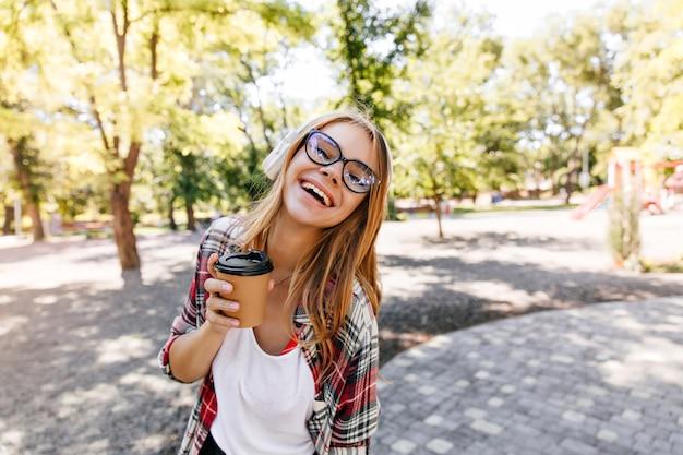Radosna biała dziewczyna w okularach wyrażających pozytywne emocje w parku. kaukaski pani korzystających na świeżym powietrzu.