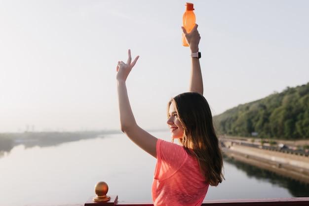 Radosna biała kobieta pozuje z uśmiechem. zewnątrz portret inspirowanej sportowej dziewczyny z butelką.