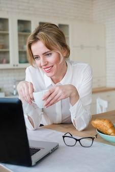 Radosna biznesowa kobieta z kawowym używa laptopem