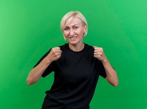 Radosna blond słowiańska kobieta w średnim wieku, patrząc z przodu, robi gest tak na białym tle na zielonej ścianie