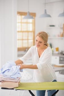 Radosna blondynka dorosły kobieta układanie rzeczy na desce do prasowania, stojąc w kuchni