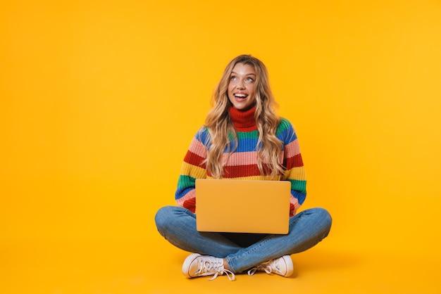 Radosna blondynka korzystająca z laptopa siedząc na podłodze odizolowanej nad żółtą ścianą