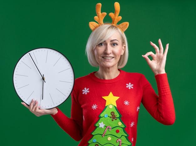 Radosna blondynka w średnim wieku ubrana w świąteczną opaskę z poroża renifera i świąteczny sweter trzyma zegar robi ok znak na białym tle na zielonej ścianie