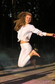 Radosna blondynka z długimi włosami skacze w parku