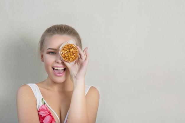 Radosna blondynka zabawy z ciastko w ręku i zasłaniając jej oko. koncepcja piekarni i słodyczy. miejsce na tekst