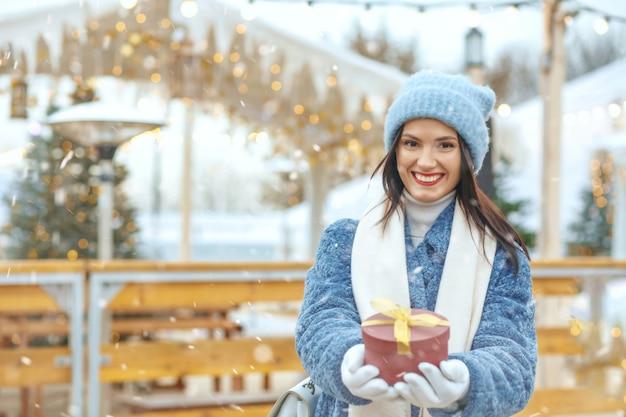 Radosna brunetka kobieta w płaszczu zimowym trzymająca pudełko na targach bożonarodzeniowych podczas opadów śniegu. miejsce na tekst