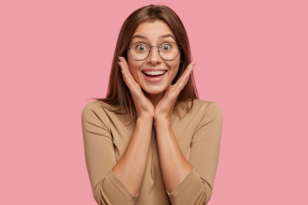 Radosna brunetka młoda europejka uśmiecha się pozytywnie, trzyma dłonie na policzkach