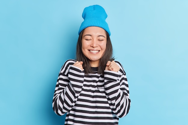 Radosna brunetka piękna azjatka zaciska pięści, świętuje coś, co sprawia, że gest tak się uśmiecha