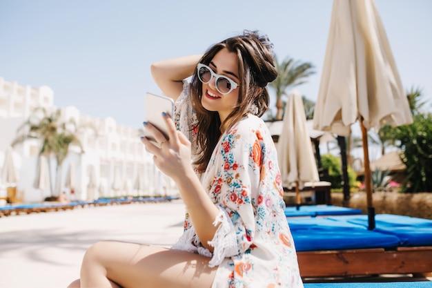 Radosna brunetka sprawdza pocztę w salonach społecznościowych, czekając na znajomych w pobliżu hotelu na wspólne kąpiele w basenie. urocza młoda kobieta siedzi na szezlongu i trzyma biały telefon w okularach przeciwsłonecznych