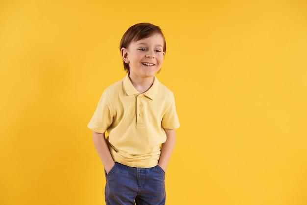 Radosna chłopiec z rękami w kieszeniach na żółtym tle.