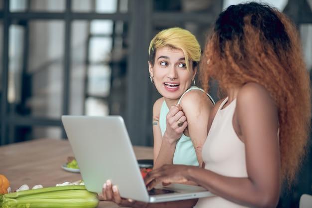 Radosna chwila. dwie młode radosne dziewczyny z laptopem w pobliżu stołu z warzywami, komunikujące się wesoło rano w kuchni
