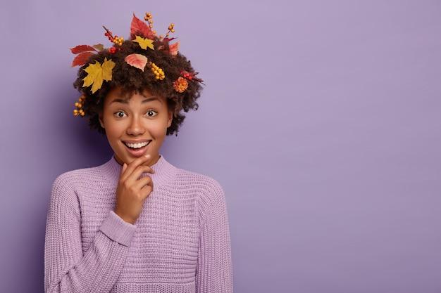 Radosna ciemnoskóra kobieta dotyka podbródka, ma beztroski radosny wyraz twarzy, uśmiecha się do kamery, ma jesienne liście i jagody w kręconych włosach, skromny przyjazny wygląd, nosi fioletowy sweter, kopiuje przestrzeń na bok