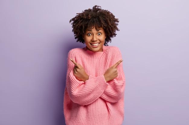 Radosna ciemnoskóra kobieta o zadowolonym wyrazie twarzy, kręconych włosach, wskazuje na boki, trzyma ręce skrzyżowane na klatce piersiowej, jest w duchu, ubrana w duży różowy sweter, odizolowana na fioletowej ścianie