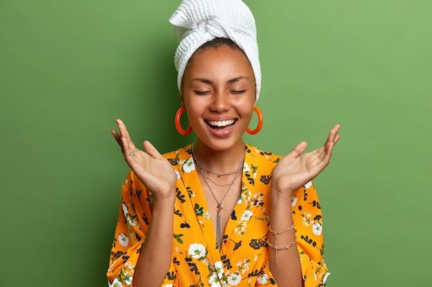 Radosna ciemnoskóra kobieta rozkłada dłonie i śmieje się radośnie zamyka oczy