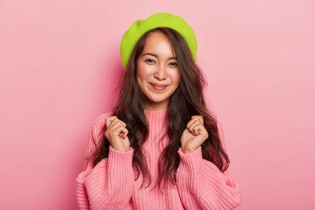 Radosna ciemnowłosa kobieta z przyjemnym uśmiechem, unosi zaciśnięte pięści, czeka na coś niesamowitego, ubrana w za duży sweter i beret