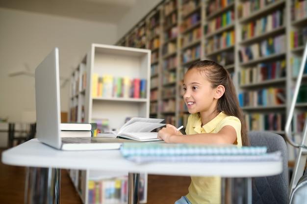 Radosna ciemnowłosa uczennica śni na jawie przy bibliotecznym stole