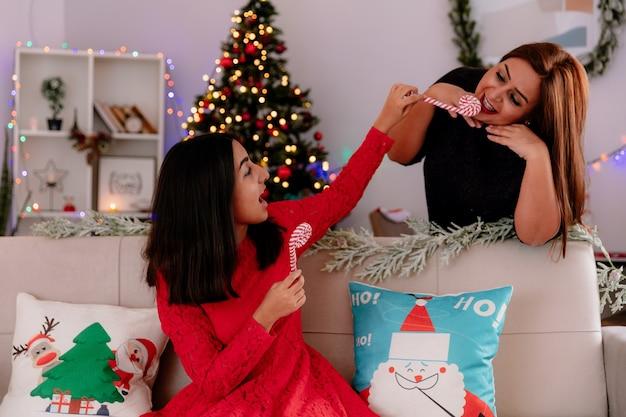 Radosna córka siedząca na kanapie trzyma cukierkową laskę w ustach zadowolonej matki, ciesząc się świątecznymi chwilami w domu