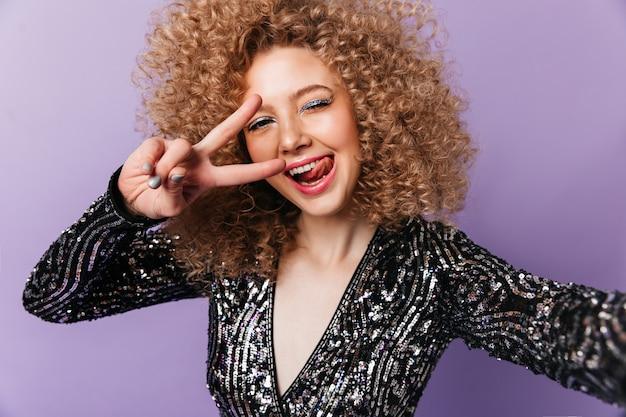 Radosna dama z niebieskimi cieniami do powiek pokazuje język i znak pokoju. kobieta w stroju disco robi selfie na odosobnionej przestrzeni.