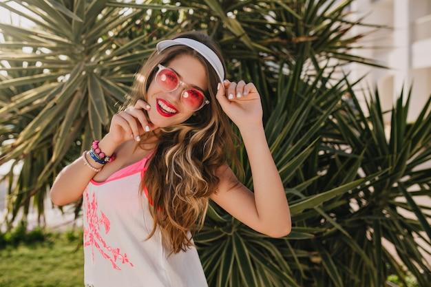 Radosna długowłosa dziewczyna w modnych różowych okularach przeciwsłonecznych, chętnie pozuje obok palmy, ciesząc się wakacjami w egzotycznym kurorcie