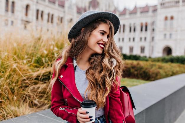 Radosna długowłosa kobieta z modnym czarnym manicure, patrząc w bok, czekając na kogoś w pobliżu starego budynku