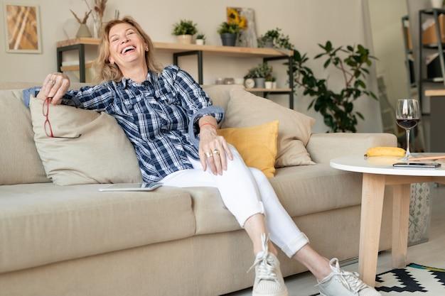 Radosna dojrzała kobieta w codziennym stroju, śmiejąca się spędzając dzień w domu i relaksując się na kanapie przy małym stoliku z lampką czerwonego wina