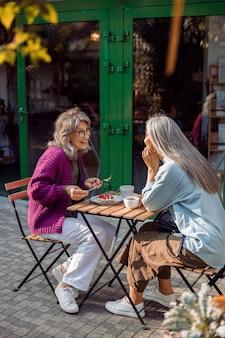 Radosna dojrzała kobieta z przyjacielem mały stolik z deserem i napojami na świeżym powietrzu
