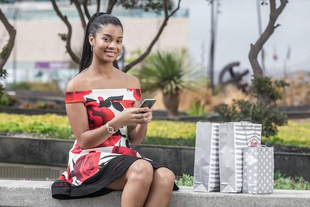 Radosna dorosła amerykanin afrykańskiego pochodzenia kobieta oddziała wzajemnie z smartphone podczas gdy siedzący na ławce przeciw centrum handlowemu