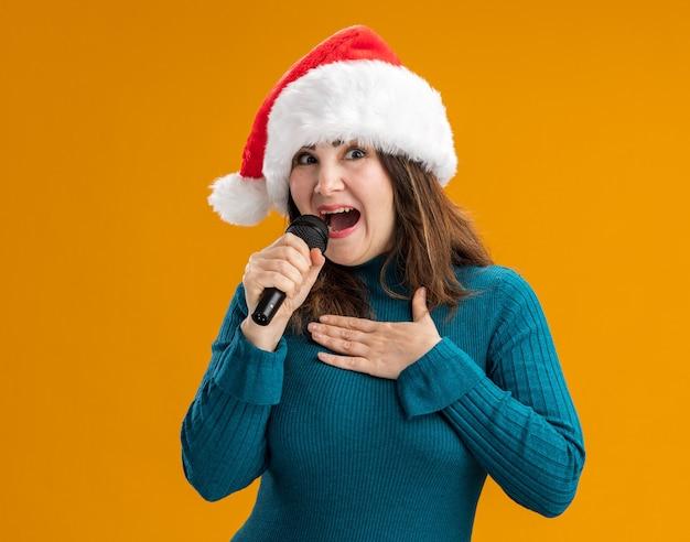 Radosna dorosła kaukaska kobieta z santa hat trzyma mikrofon i kładzie rękę na klatce piersiowej na białym tle na pomarańczowym tle z miejsca na kopię