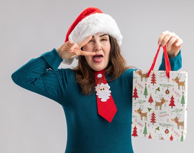 Radosna dorosła kobieta rasy kaukaskiej z santa hat i krawatem santa wystaje język i trzyma papierowe pudełko na białym tle z miejsca na kopię