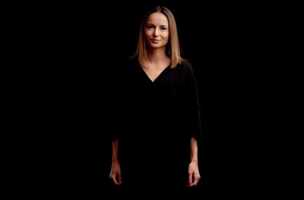 Radosna dorosła kobieta stojąca na czarnym tle