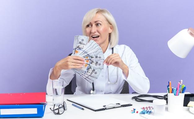 Radosna dorosła słowiańska lekarka w szacie medycznej ze stetoskopem siedząca przy biurku z narzędziami biurowymi trzymającymi pieniądze i patrząca na bok odizolowana na fioletowym tle z kopią miejsca